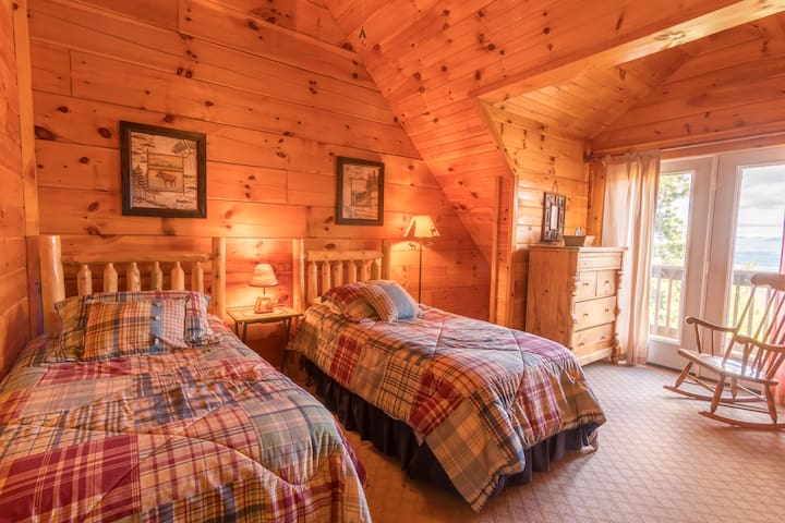 Twin beds in bedroom #3, with vaulted ceilings and its own private balcony overlooking the Blue Ridge Mountains.