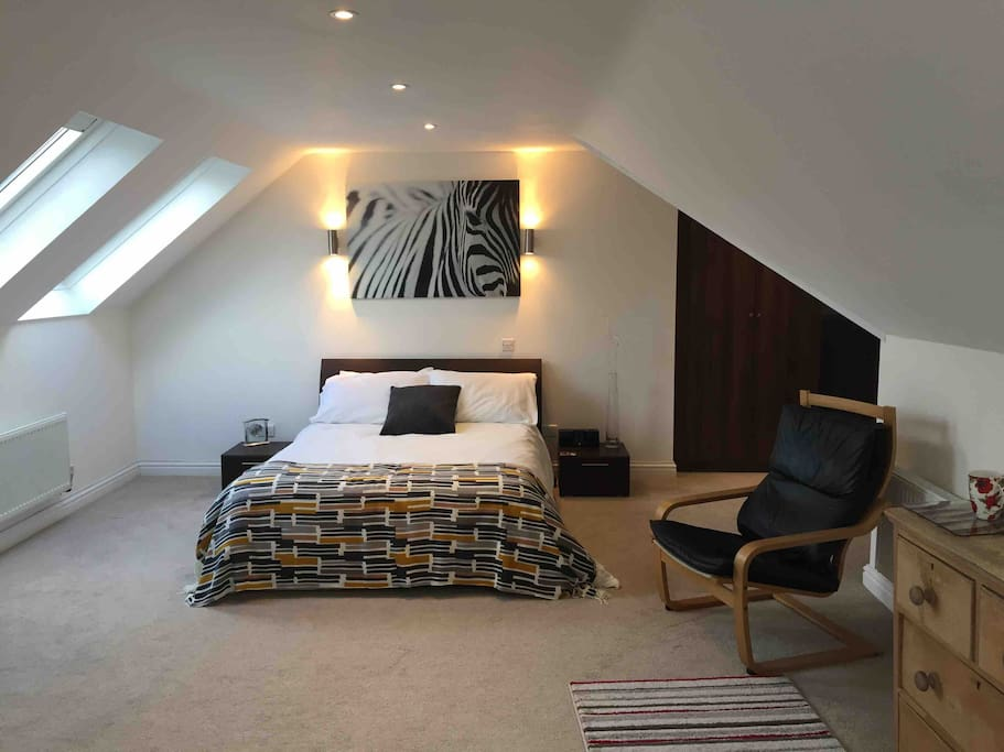 This room is huge! There are 3 roof lights with blackout blinds, storage for your clothes and Wi-Fi . Relax in a comfortable chair watching the 32 inch smart tv with Virgin Media channels or connect to your Netflix account.