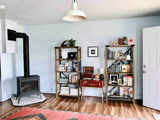 Cozy gas stove, a handmade table crafted from a repurposed vintage suitcase, and two shelves of A+ books and games.