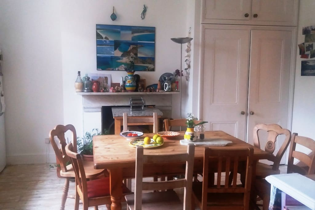 Very large family kitchen with pine table, pine floorboards and original marble fireplace