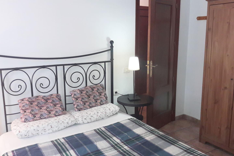 Habitación exterior con cama doble, armario, comoda, y mesitas de noche.