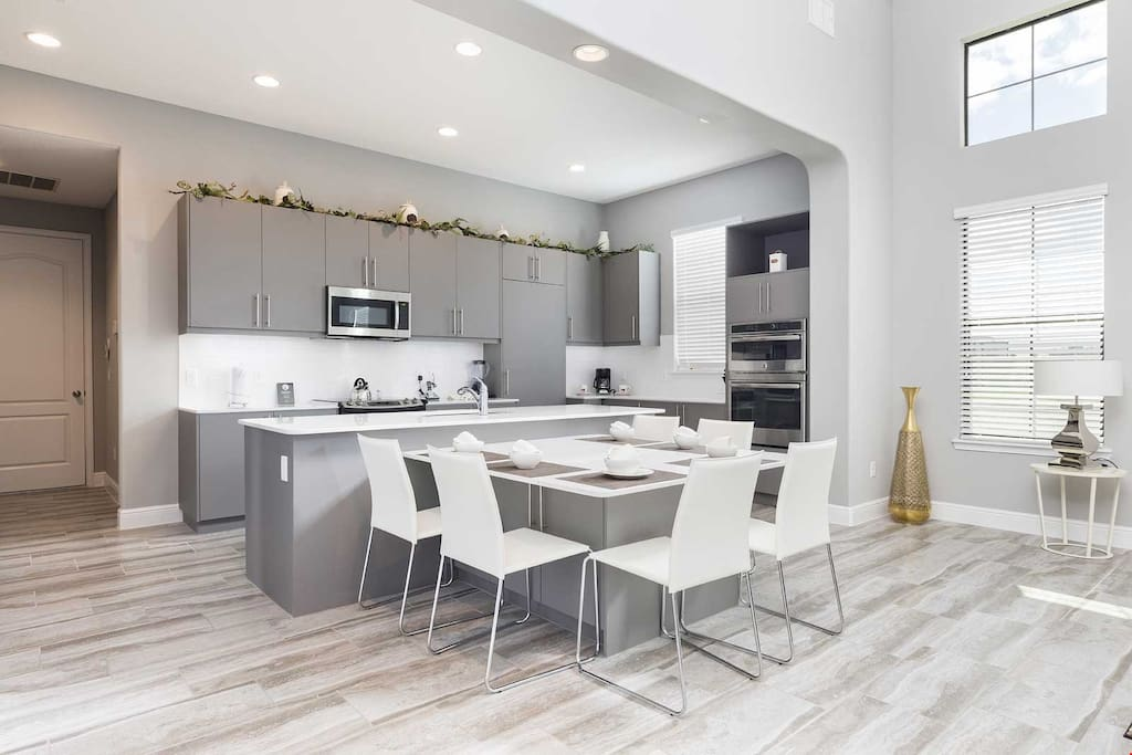 The bright and modern living area features a dining table and a full, grand kitchen.