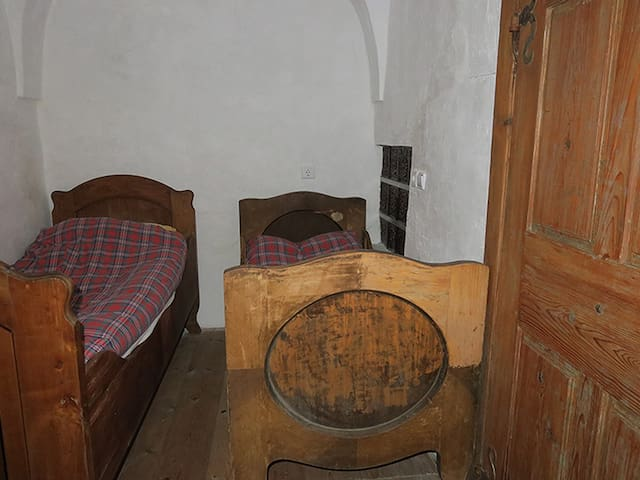 The bedroom is relatively narrow and contains three vintage beds. One of these is shorter than the others (1.75 m) because, in the past, people were smaller! On the right-hand-side, you can see how the traditional wood stove is built in the wall.