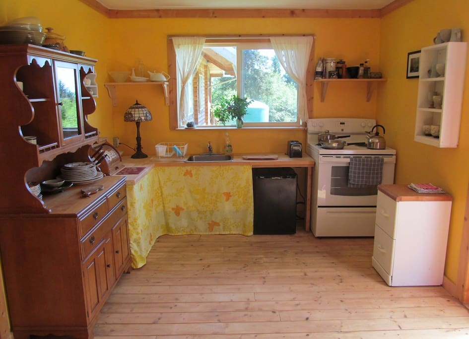 Sunny kitchen with bar fridge and stove