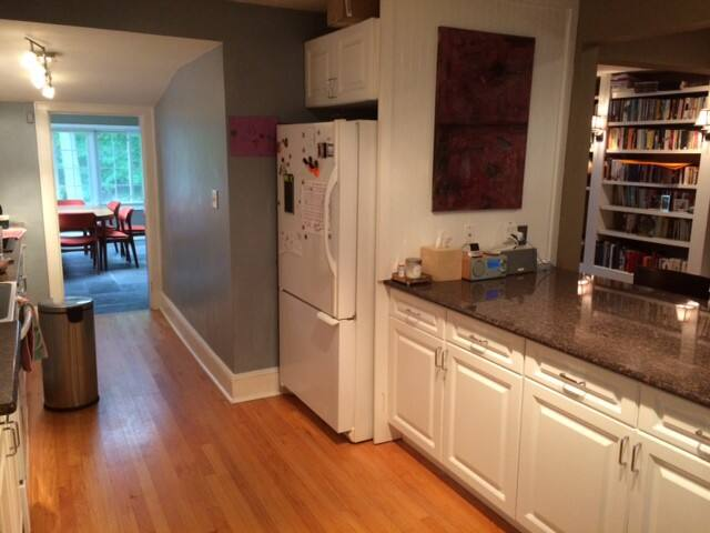 Kitchen with open counter and barstools at right.