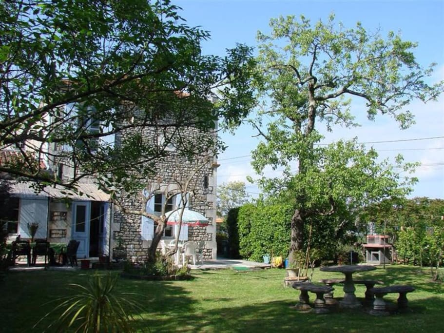 Vue de la maison depuis le parc avec le barbecue à droite.