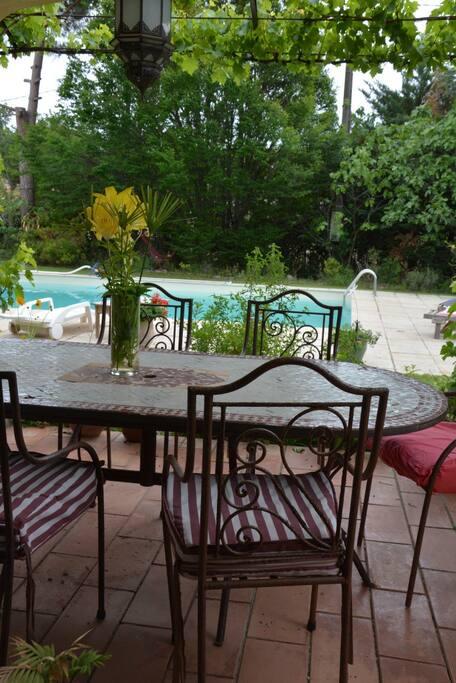 Terrasse avec grande table marocaine donnant sur le jardin et la piscine