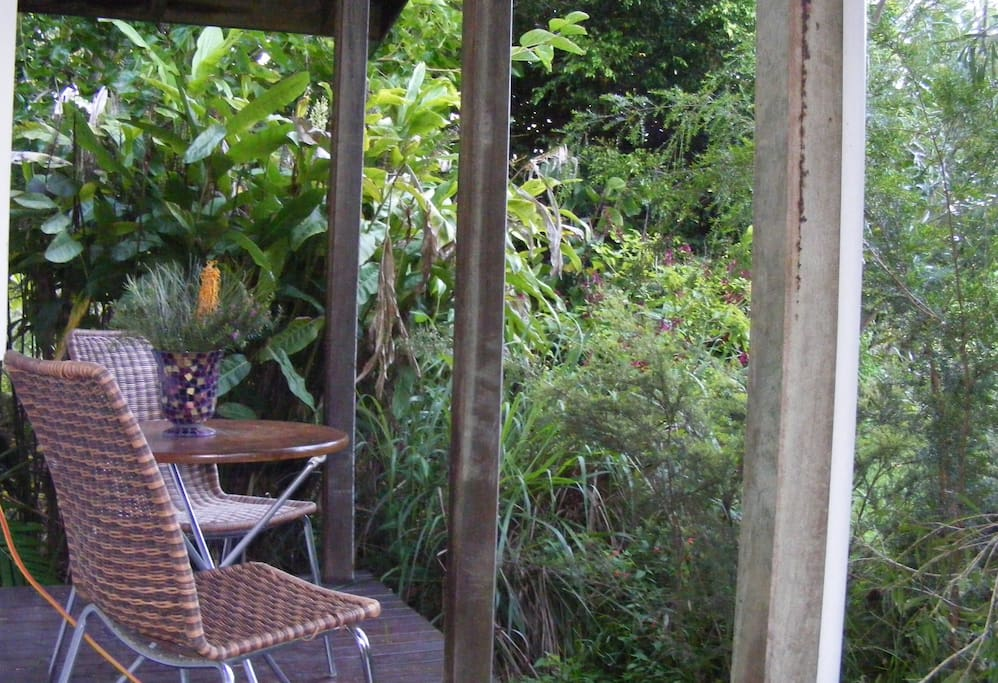 Private verandah with table setting surrounded by lush native gardens