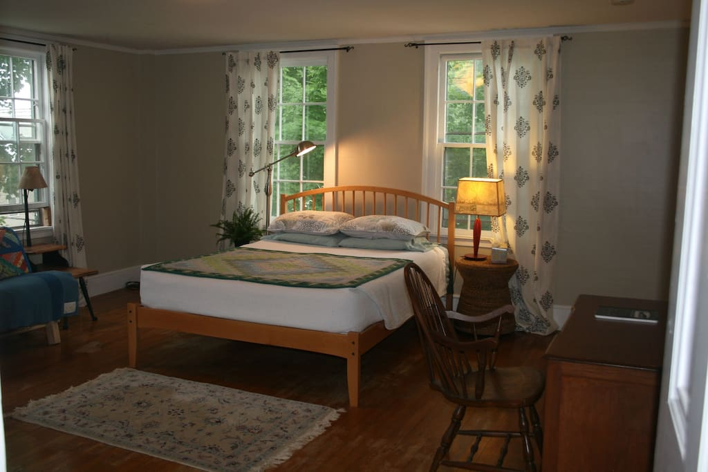 Our second floor  apartment bedroom has 4 large windows and  lots of warm light.  There is a queen size bed with lots of pillows and a queen size futon.