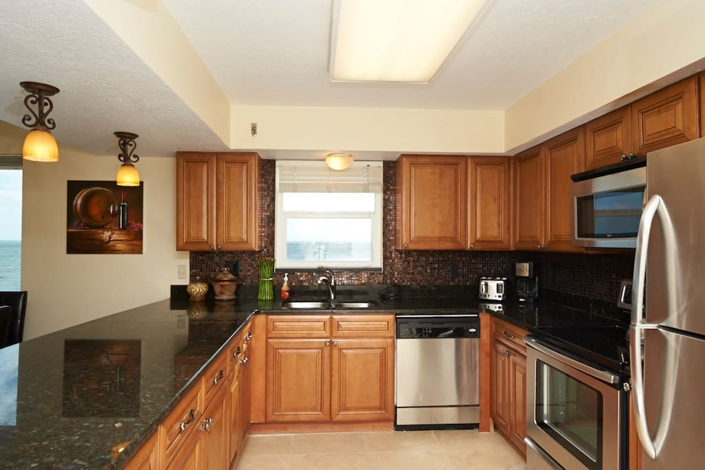 Beautiful kitchen with granite counters and a view of the ocean while cooking!
