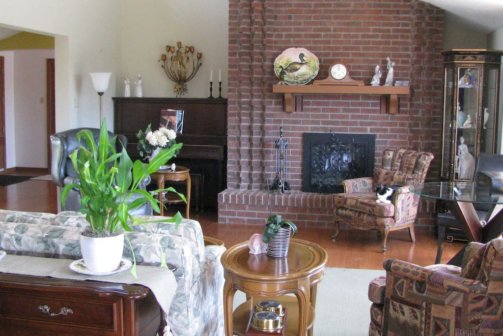 Bright comfortable living room with library, games and wood burning fireplace.