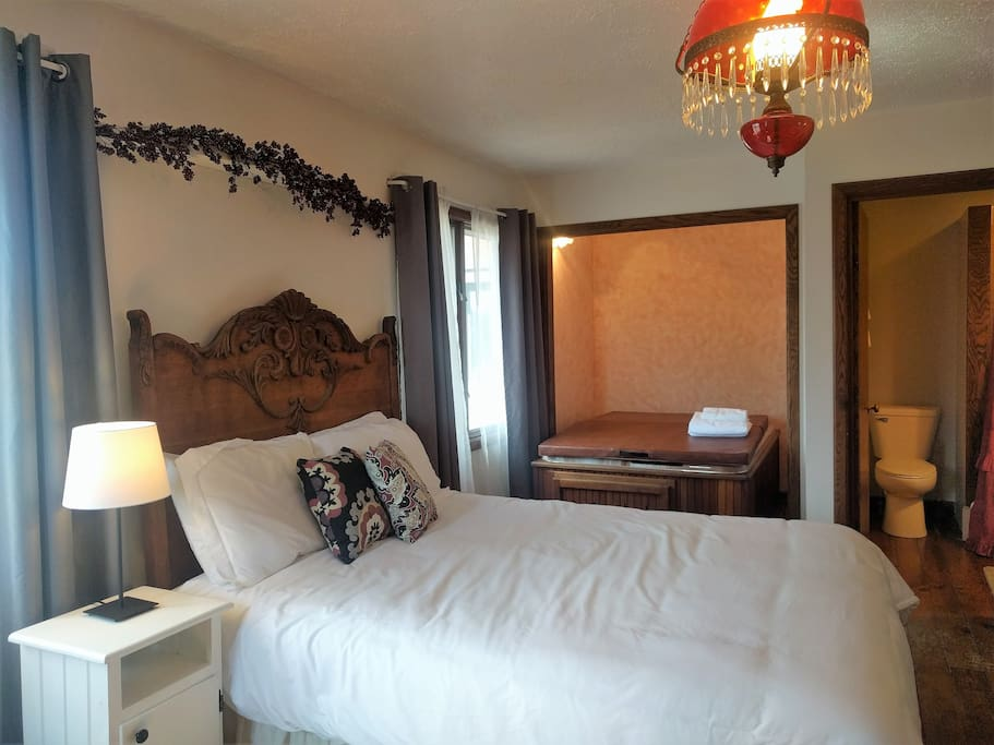 Queen bed, hot tub, & private bathroom with stall shower.