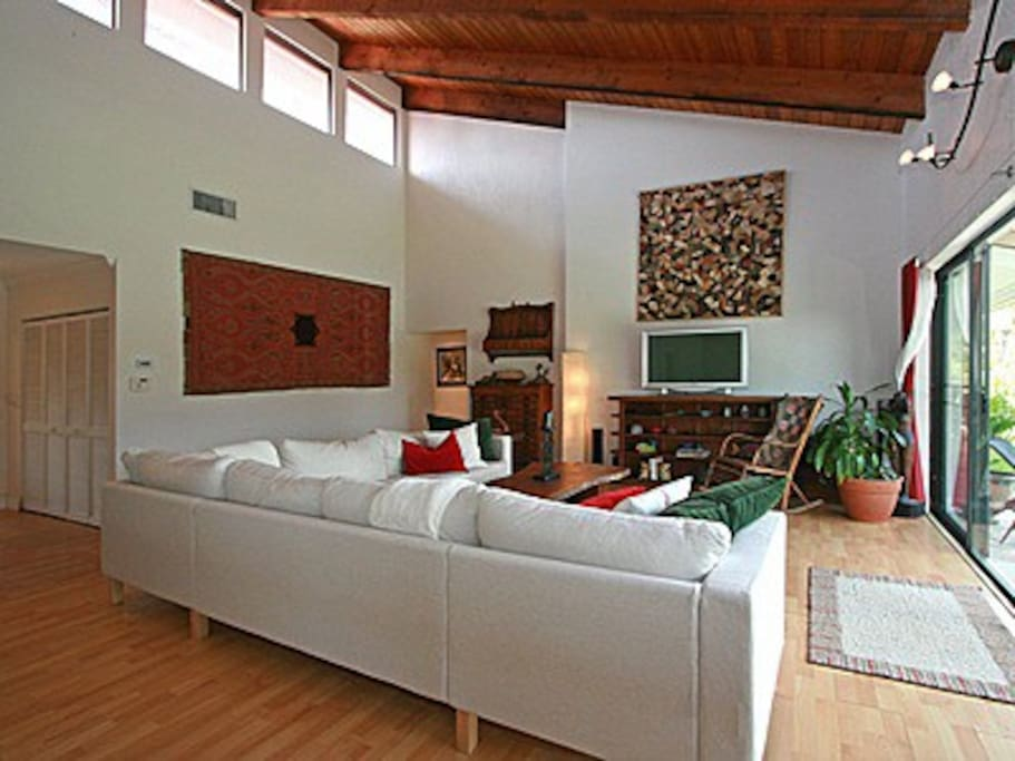 Living Room with vaulted ceiling, skylights, lake and pool view, open to dining room