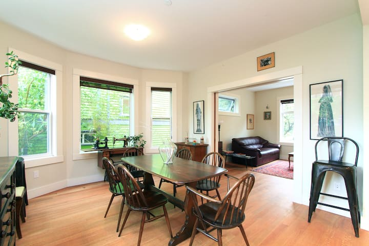 Open living room and dining room with oak floors.
