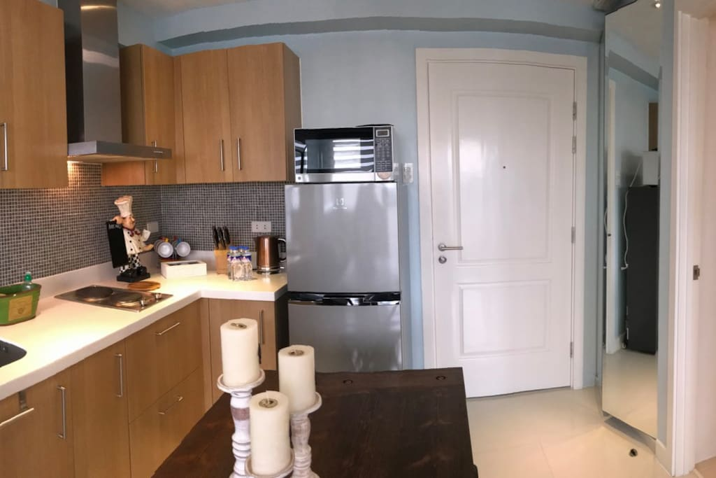 Kitchen with 4 seater dining table, fridge, microwave, cooktop and overhead exhaust fan