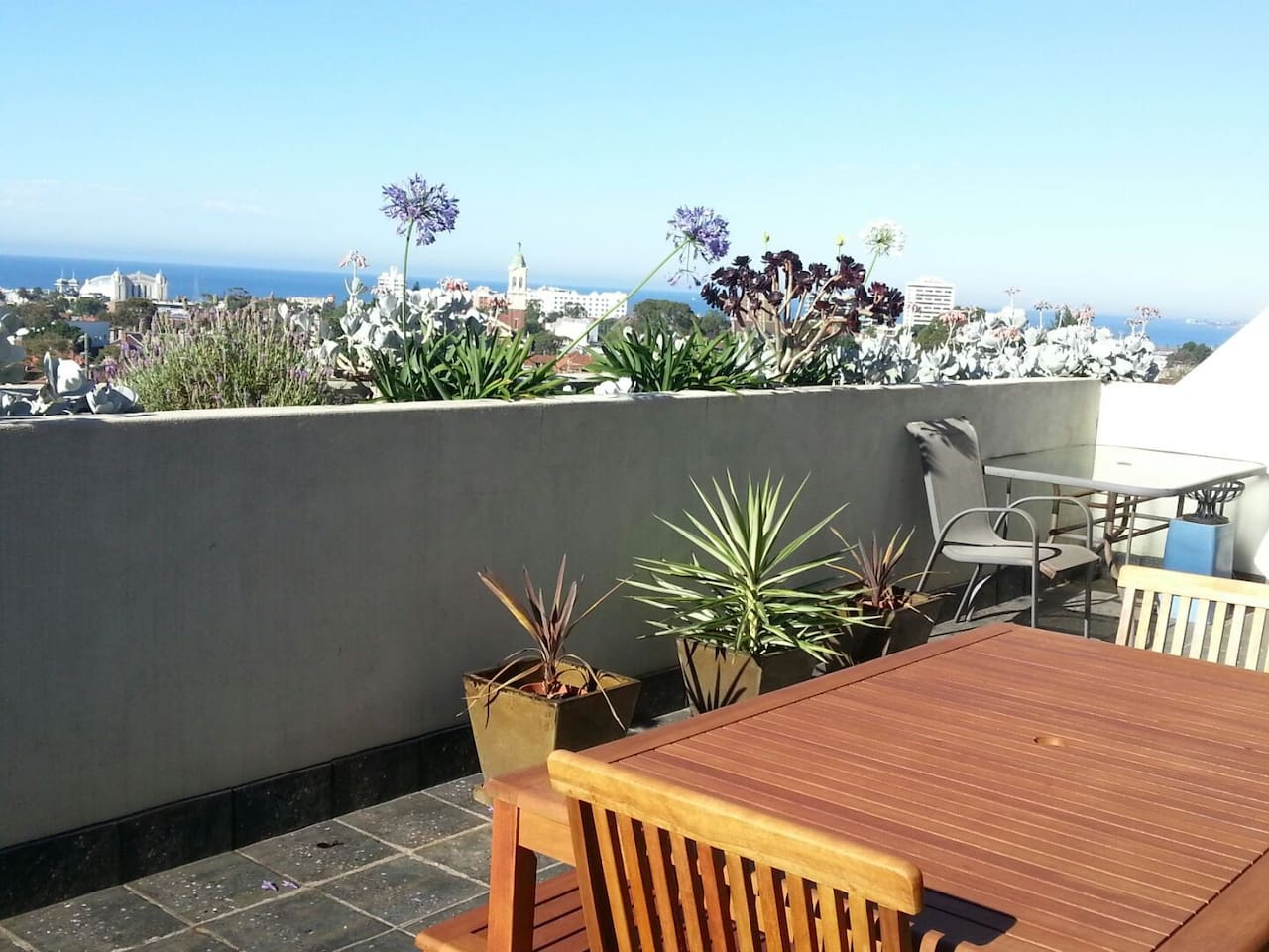 Large outdoor patio with table and chairs plus sun lounges.