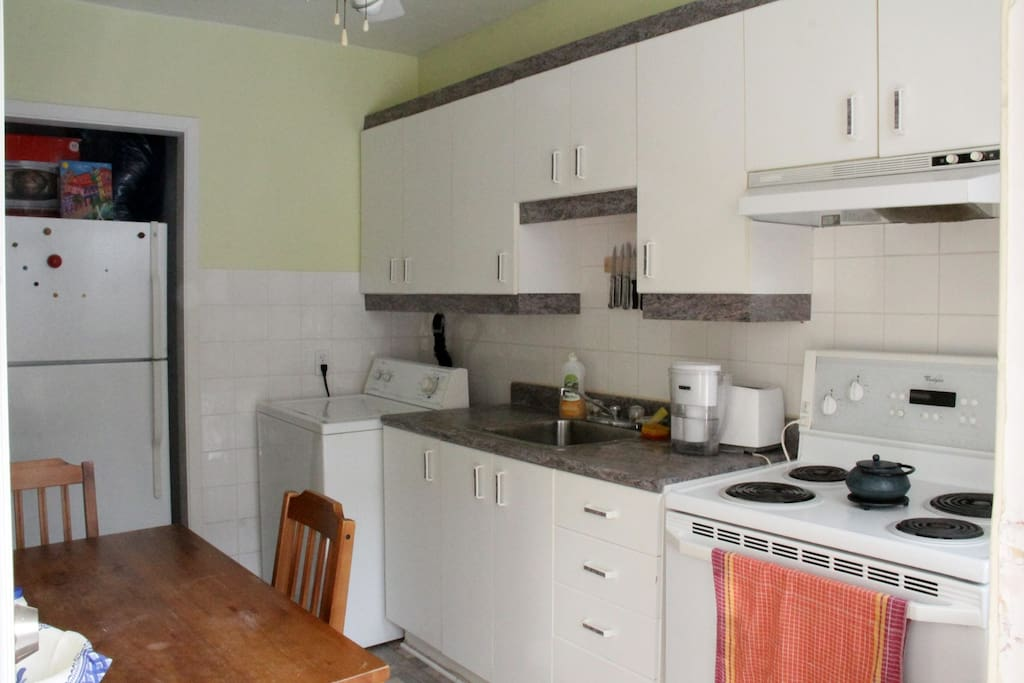 The kitchen has all the amenities, a table for three and a washing machine.