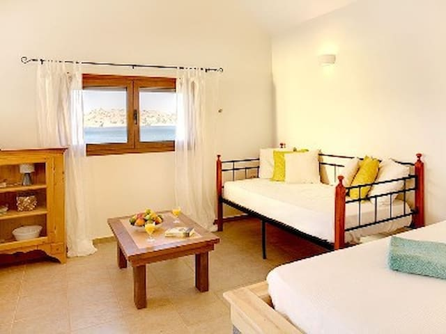 The large studio room of the cottage with the large double bed and the daybed/singlebed