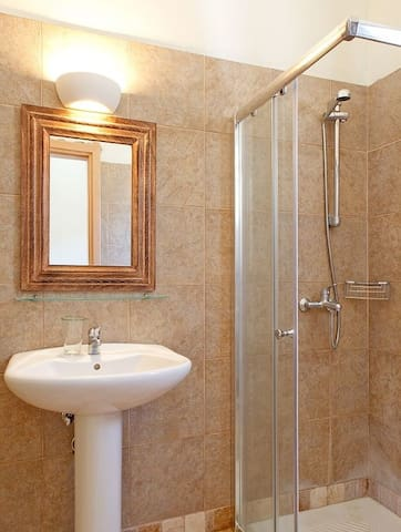 The bathroom with shower, sink and toilet.