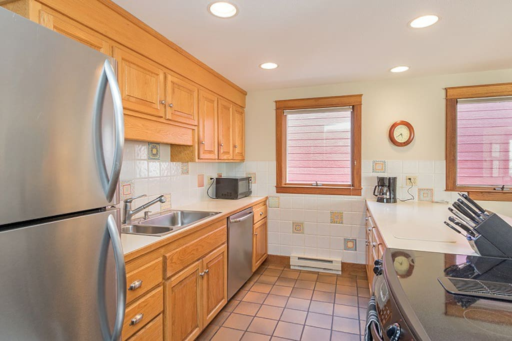 Galley kitchen with stainless appliances, open to living and dining area