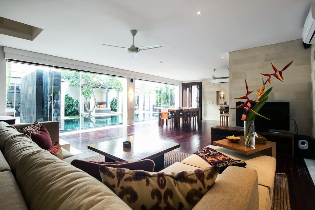 Large and spacious living, dining and kitchen area looking out at the pool.