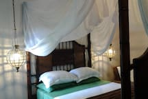 Bedroom with feature brass lighting, queen size bed with nets