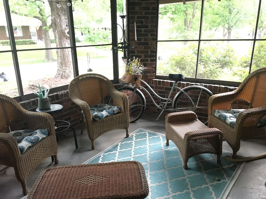 Screened in front porch is perfect for enjoying wine at night or coffee in the morning.
