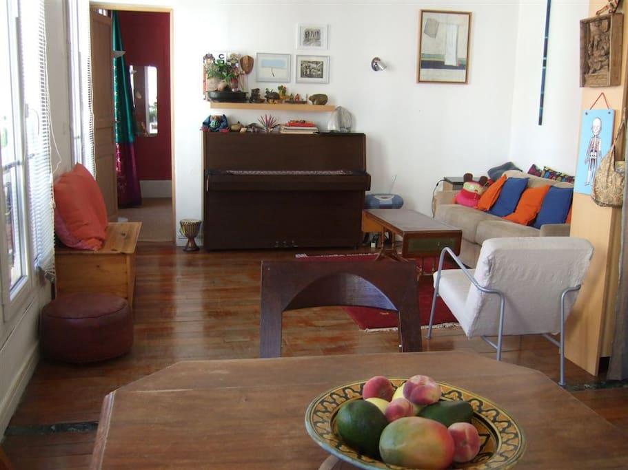 Salon avec Piano et un canapé/lit double place.