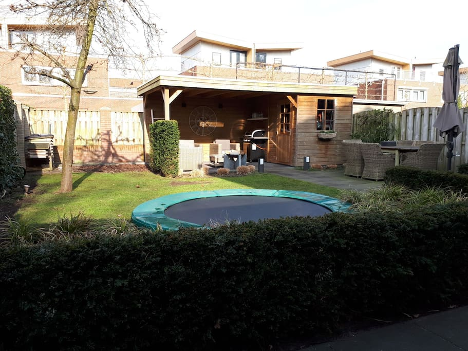 Garden with play area and lounge seats.