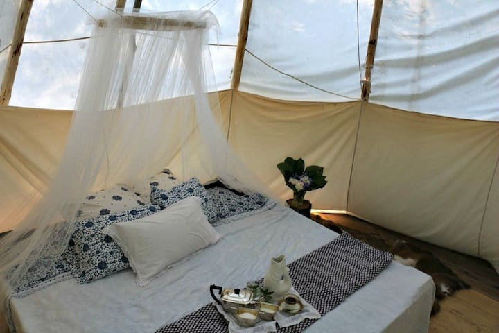 In summer we remove the woodstove and make the bed a king - bringing your sleepingbags is standard - but linens can be provided for $20 extra.  We do not use the mosquito net any longer but have this image so you can see the king size bed arrangement in SUMMER only.