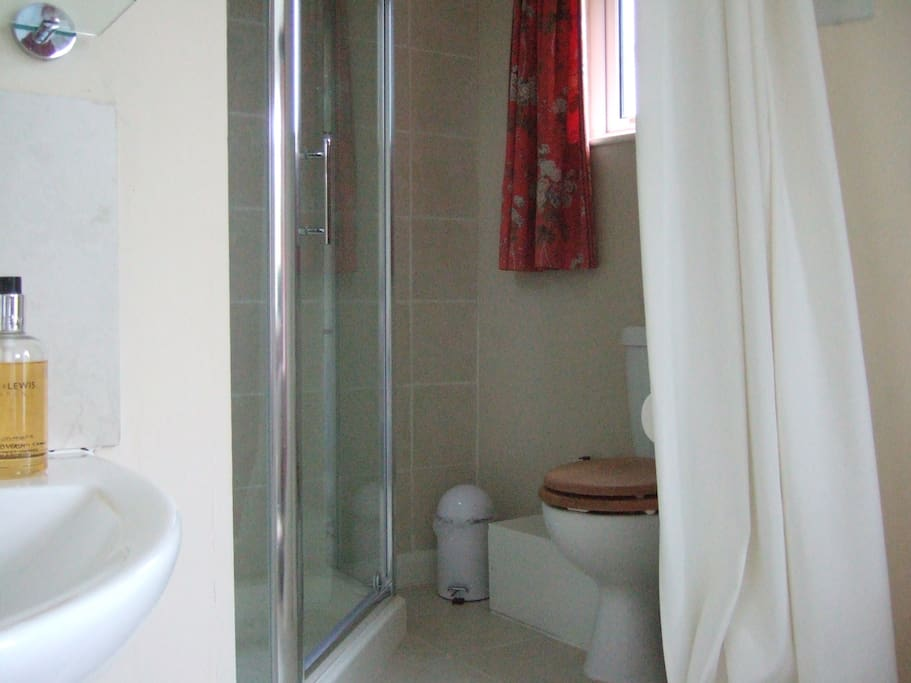 The curtained ensuite bathroom has a shower.