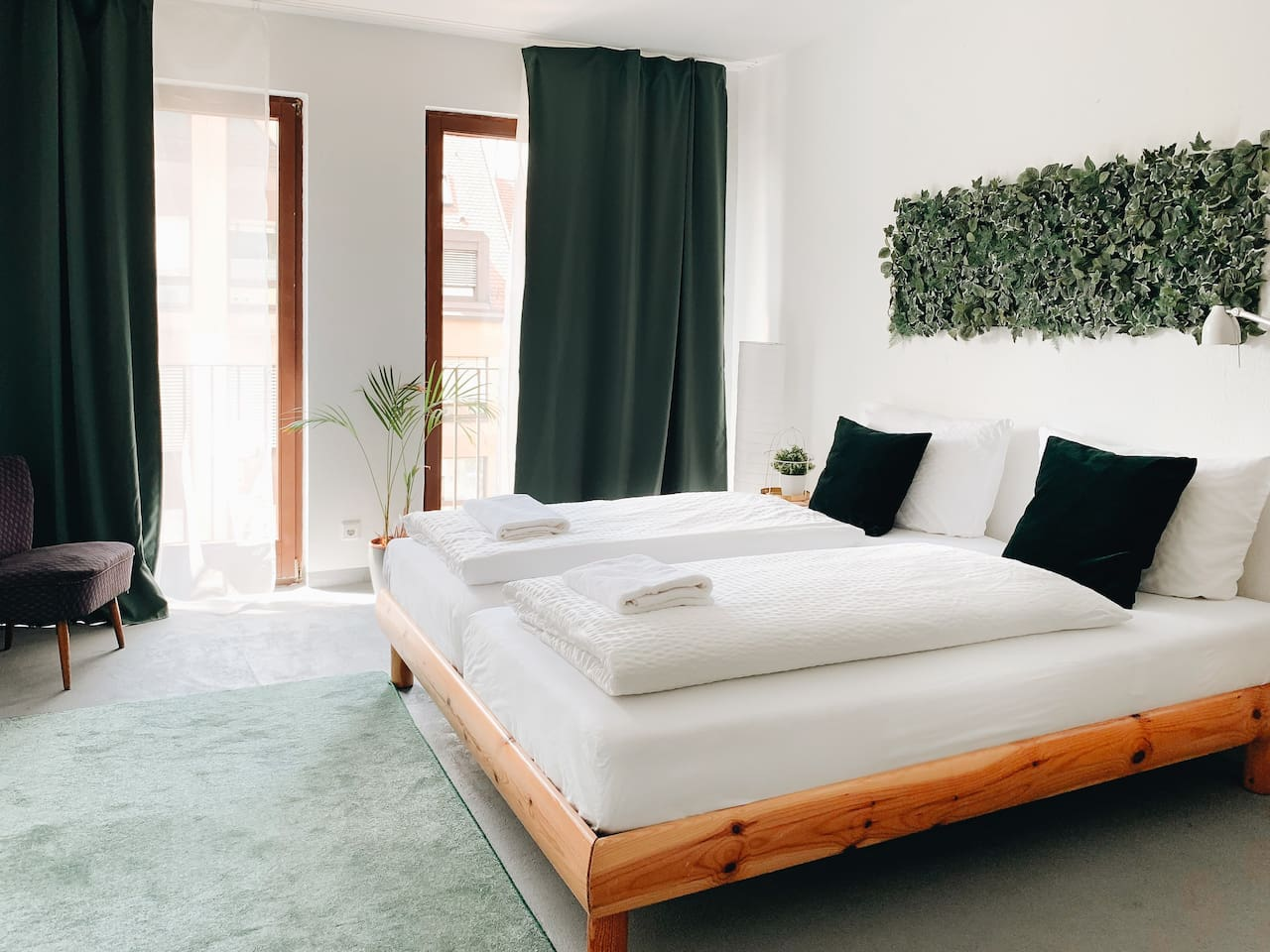 The bright studio apartment with large windows and a jungle theme