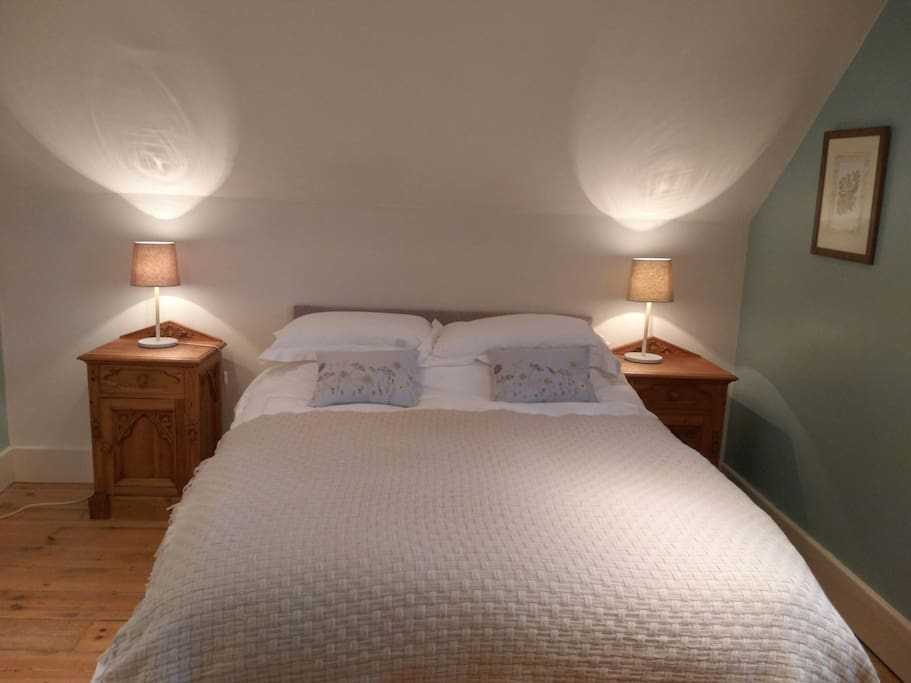 Each side of the bed has ample space and their own bedside tables and lamps.