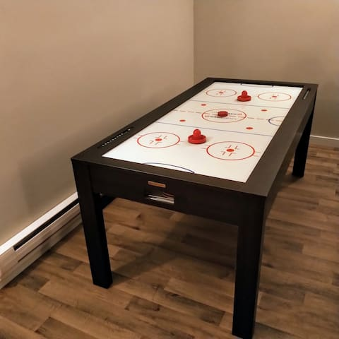 Games table with air hockey, ping pong, and cards table in basement.