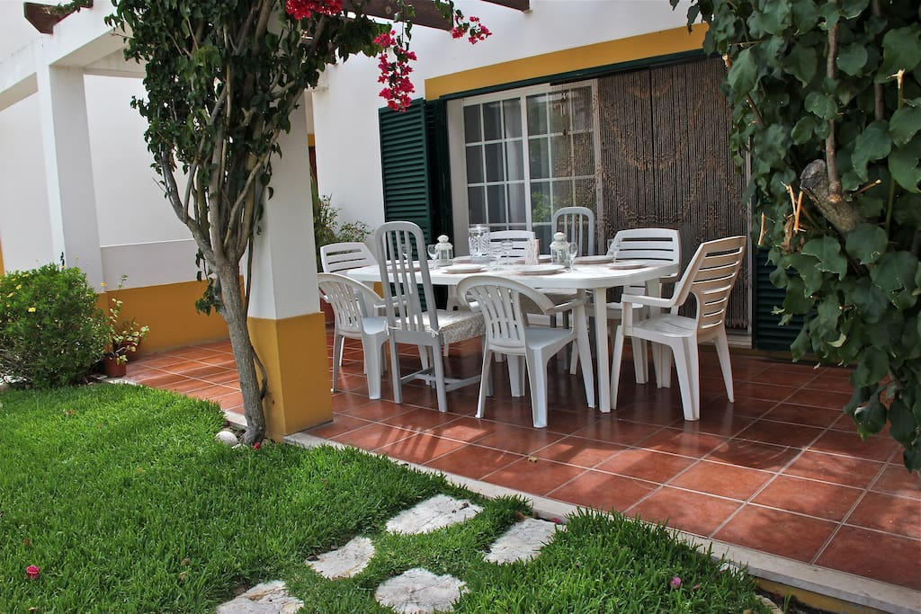Porch with table and chairs for dining or lounging under the buganvílea