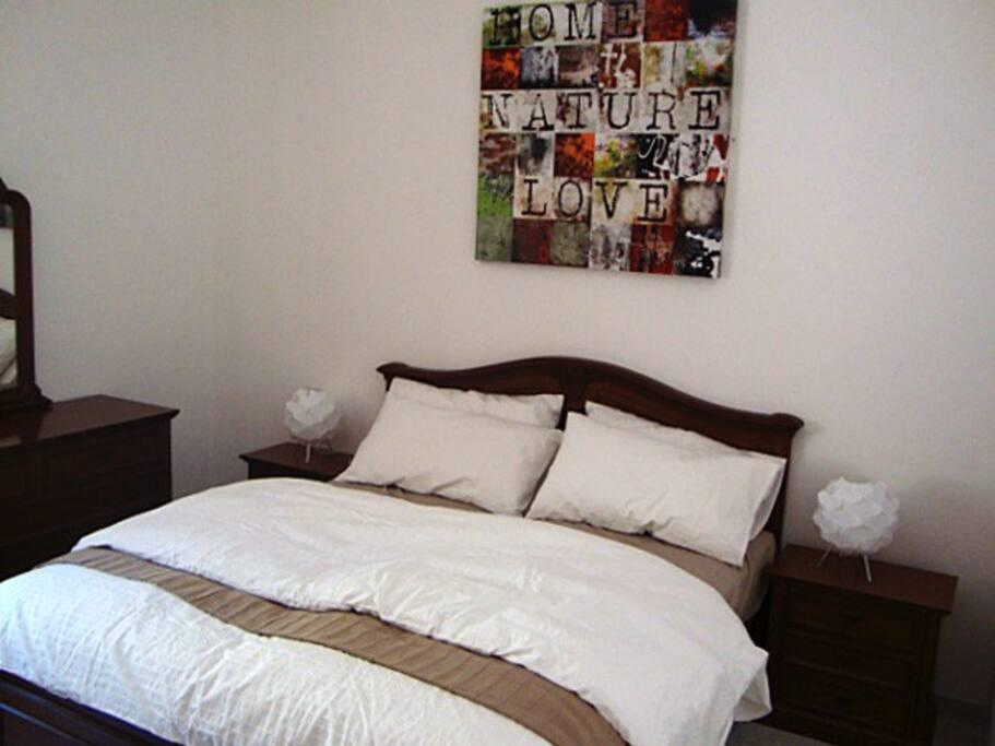 Schlafzimmer mit Doppelbett, Kleiderschrank, Kommode, Nachttischchen mit Lampe