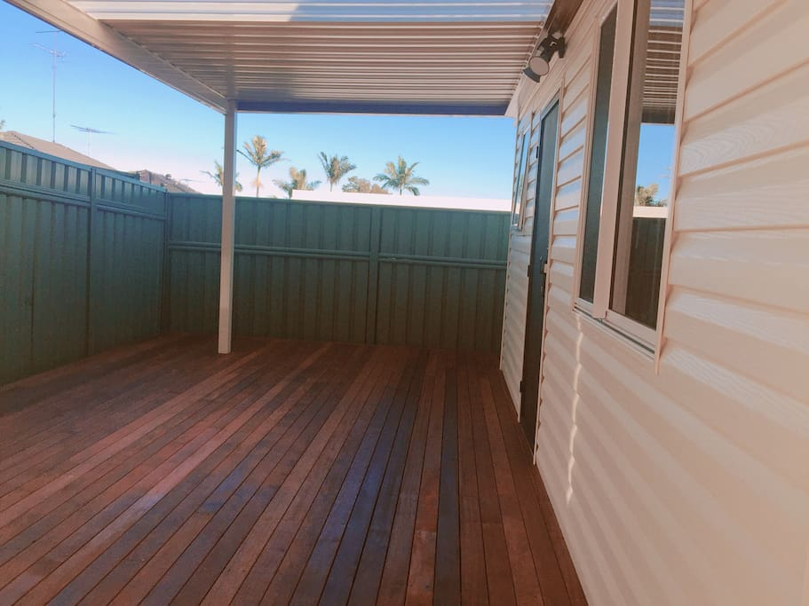 Backyard with timber decking and shade on top.