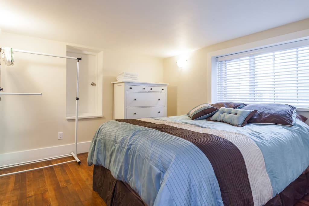 Queen size bed, ample clothing storage with dresser and hanging rack