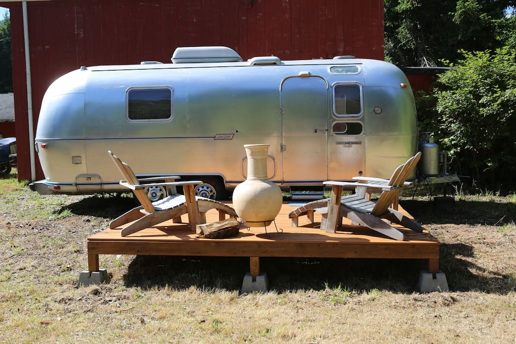 Heres the Front view of the Airstream showing the deck  which is connected right to the doorstep of the Airstream, comfortable handmade Adirondack chairs for relaxing.