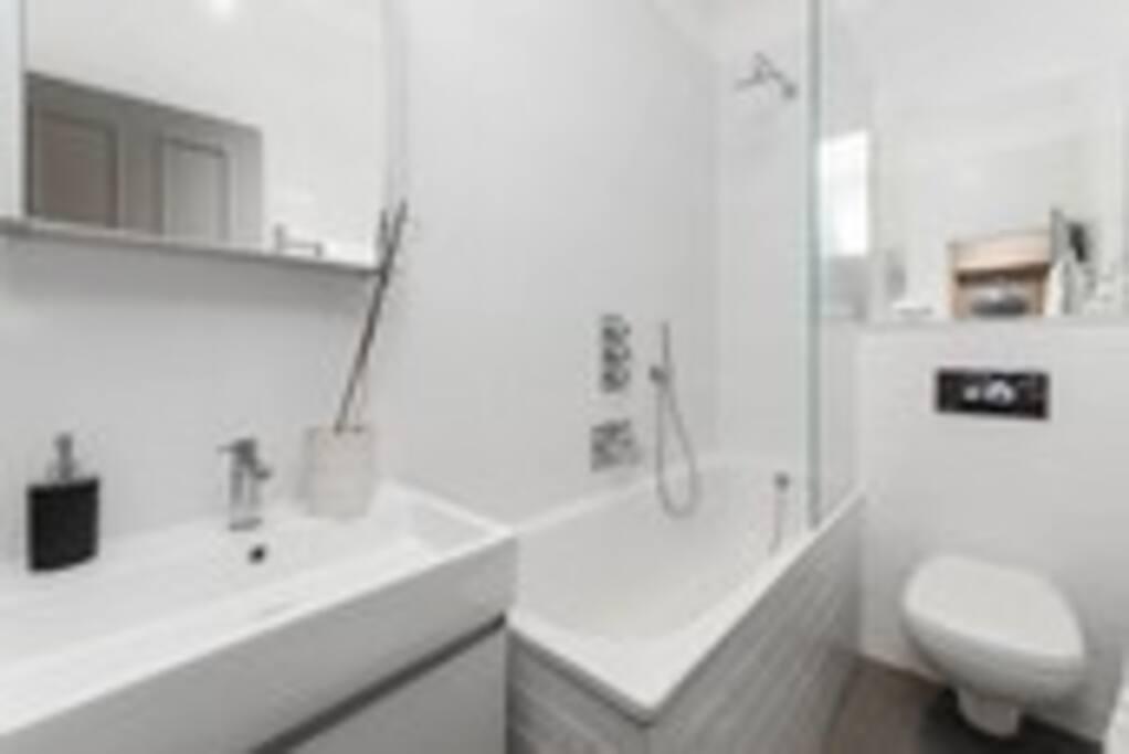 Bathroom with full sized bath and rain shower