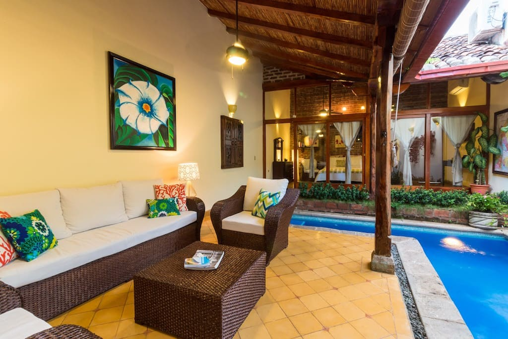 The extra wide sofa and two club chairs were custom made for Casa Romantica in December 2017. Local artisans built the actual furniture by hand, then doubled the cushion height for a more comfortable and relaxing experience (not common in Nicaragua to have deep seating or thicker cushions). Your own private indoor / outdoor pool right in the living room! Large flatscreen TV is directly behind this shot, so it can be seen from sitting area and pool (also has US Netflix, in addition to regular cable)