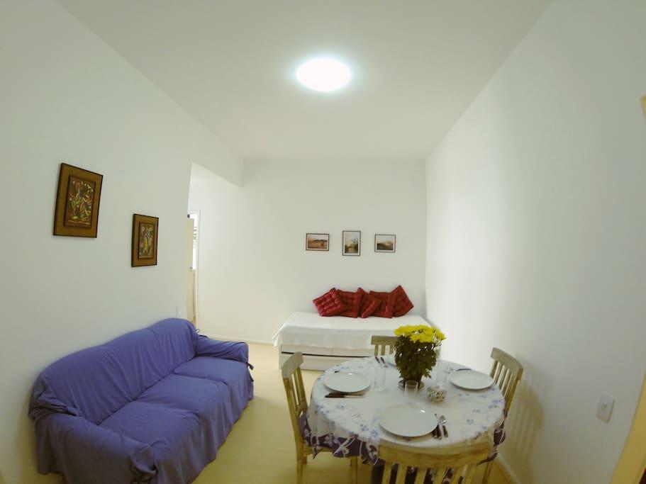 Sala clara e arejada com mesa com quatro cadeiras, sofá de três lugares e bi-cama.