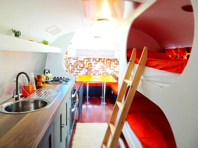 Fully equipped galley kitchen (with oven, grill, hob), bunk beds, large dining table with seating and wood burner