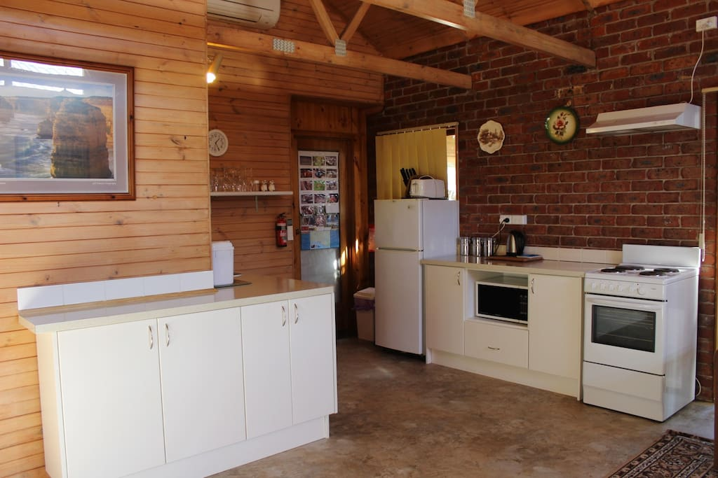 Fully equipped kitchen with fridge, stove, microwave.