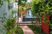 The pool, framed by greenery and brightly painted geometric shapes, is the perfect place to cool off after a day checking out the city.