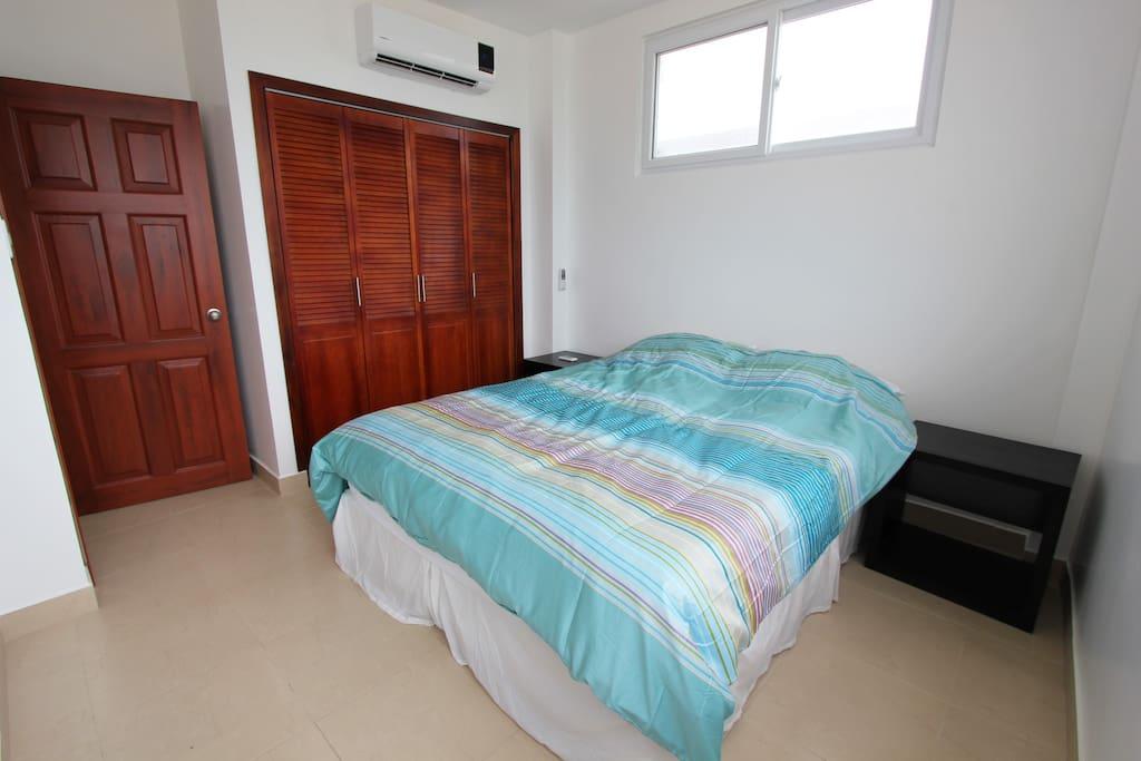 Guest bedroom with ceiling fan and air conditioning unit