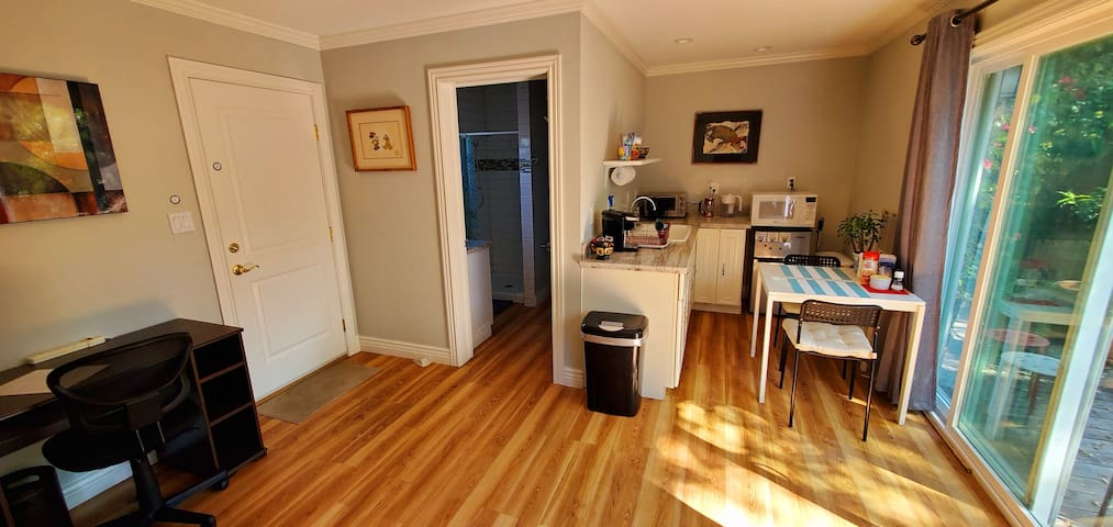 Wide-angle photo of the kitchen and entrance to the bathroom. The kitchen area: Toaster, microwave, fridge, sink.