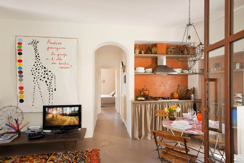 One's first impressions are of a light and airy space. On the right is the kitchen and dining area, to the left a comfortable, linen-covered sofa opposite of the fireplace.