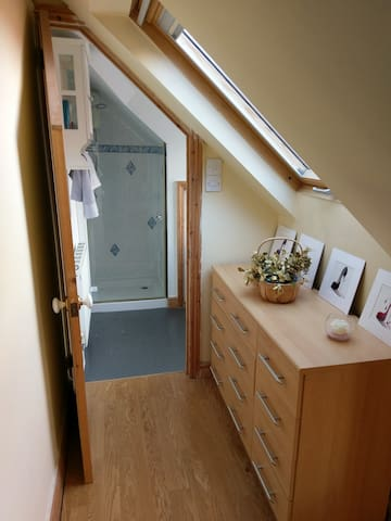Bedroom through to bathroom. Velux window and drawer storage.