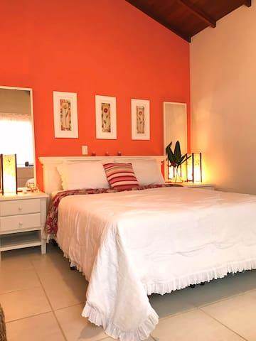 Suite Master com cama Queen size, Ar condicionado tipo Split,  ventilador de teto e varanda com vista para a piscina, jardim e mata Atlântica.